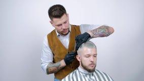 Un giovane tipo ottiene un taglio di capelli con le forbici dei capelli con un pettine stock footage