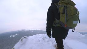 Un giovane, un turista, sta sull'orlo di una montagna innevata ed ammira la cima della montagna stock footage