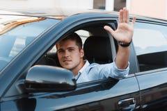 Un giovane in un'automobile ha attaccato il suo distribuisce la finestra L'uomo approva Immagini Stock