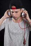 Un giovane in un cappuccio che ascolta intento la musica sulle cuffie Fotografia Stock Libera da Diritti