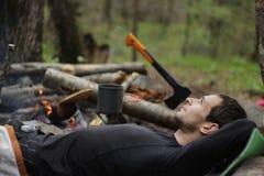 Un giovane in un rivestimento nero che si trova intorno al fuoco di accampamento Fotografia Stock