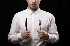 Un giovane in una camicia bianca su un fondo nero Fotografie Stock