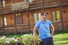 Un giovane in una camicia blu e shorts blu vicino ai carretti di legno decorativi con i fiori, su un fondo di stile rustico Fotografia Stock Libera da Diritti