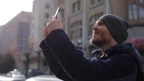 Un giovane in una giacca blu ed in un cappuccio grigio spara una città sul telefono stock footage