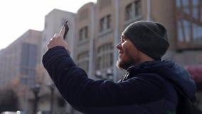 Un giovane in una giacca blu ed in un cappuccio grigio spara una città sul telefono archivi video