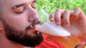 Un giovane in una maglietta rossa beve la birra con piacere Primo piano Il tipo con la barba ha bevuto un alcoolizzato schiumoso archivi video