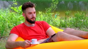 Un giovane in una maglietta rossa con una tazza di caffè sta trovandosi su un sofà aerato contro lo sfondo del fiume Il tipo video d archivio