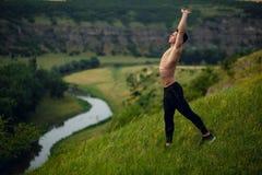 Un giovane uomo adatto allegro senza camicia che fa allungando gli esercizi esterni sul fondo del paesaggio Vista orizzontale fotografie stock libere da diritti