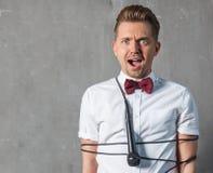 Un giovane uomo affascinante attraente in una camicia bianca e in un butterfl fotografia stock