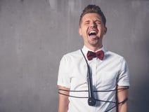 Un giovane uomo affascinante attraente in una camicia bianca e in un butterfl fotografia stock libera da diritti