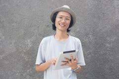Un giovane uomo asiatico creativo atractive con il cappello ed i vetri facendo uso della compressa e sorridere della fedora alla  fotografia stock