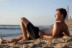 Un giovane uomo attraente si trova sulla sabbia vicino al mare ed osserva la natura fotografia stock