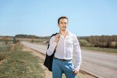 Un giovane uomo attraente sta al pomeriggio su una strada rurale soleggiata fotografia stock