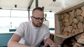 Un giovane, uomo barbuto con i vetri si siede sul terrazzo e sui tipi alla tastiera del suo computer portatile video d archivio
