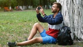 Un giovane uomo barbuto si siede sotto un albero nel parco e prende le foto di bellezza intorno lui Il tipo prende un selfie video d archivio