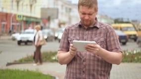 Un giovane uomo barbuto utilizza una compressa digitale accanto ad una strada di grande traffico archivi video