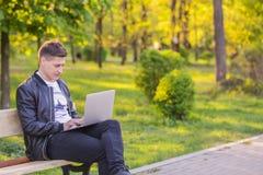Un giovane uomo bello è sedentesi e lavorante nel parco con un computer portatile Le free lance del tipo lavorano fuori Fotografie Stock Libere da Diritti