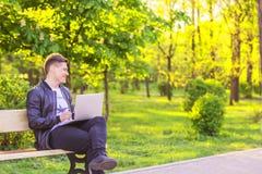 Un giovane uomo bello è sedentesi e lavorante nel parco con un computer portatile Le free lance del tipo lavorano fuori e sorriso Fotografia Stock