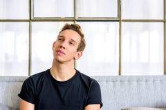 Un giovane uomo bello che si rilassa sul sof? in un apartm di stile del sottotetto fotografia stock