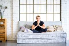 Un giovane uomo bello che si rilassa sul sof? in un apartm di stile del sottotetto fotografia stock libera da diritti