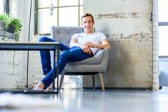 Un giovane uomo bello che si rilassa in una poltrona in uno stile APAR del sottotetto immagine stock libera da diritti