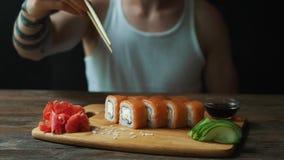 Un giovane uomo bello sta mangiando i rotoli di sushi con i bastoncini in un ristorante giapponese stock footage