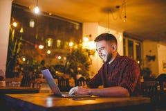 Un giovane uomo caucasico bello con la barba ed il sorriso a trentadue denti in una camicia a quadretti rossa sta lavorando dietr immagine stock