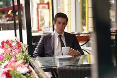 Un giovane uomo d'affari è venuto a pranzare in un caffè, si siede ad una tavola ed aspetta qualcuno fotografie stock libere da diritti