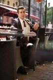Un giovane uomo d'affari è venuto a pranzare in un caffè, si siede ad una tavola ed aspetta qualcuno immagine stock libera da diritti