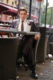 Un giovane uomo d'affari è venuto a pranzare in un caffè, si siede ad una tavola ed aspetta qualcuno fotografia stock libera da diritti
