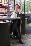 Un giovane uomo d'affari è venuto a pranzare in un caffè, si siede ad una tavola ed aspetta qualcuno immagini stock
