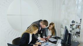 Un giovane uomo d'affari alla moda in una sala per conferenze collabora con il suo gruppo su un business plan creativo video d archivio