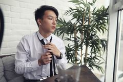 Un giovane uomo d'affari asiatico sta aspettando un partner in un caffè Bu fotografia stock libera da diritti