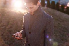 Un giovane uomo d'affari bello facendo uso del suo telefono fotografia stock libera da diritti