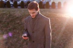 Un giovane uomo d'affari bello facendo uso del suo telefono e condizione sulla via nella sera immagini stock