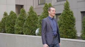 Un giovane uomo d'affari che cammina con le cuffie senza fili e discute a fondo la telefonata archivi video