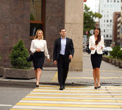 Un giovane uomo d'affari che cammina sulla via con i loro segretari Immagine Stock Libera da Diritti