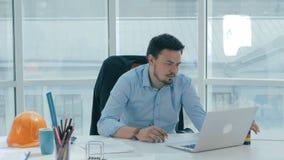 Un giovane uomo d'affari sta lavorando all'ufficio luminoso moderno video d archivio
