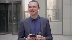 Un giovane uomo d'affari sta stando sulla via e sta sorridendo con cuffie senza fili in sue orecchie stock footage