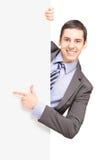 Un giovane uomo d'affari in vestito che indica su un pannello in bianco Fotografia Stock