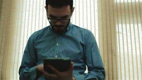 Un giovane uomo d'affari in vetri facendo uso di una compressa archivi video