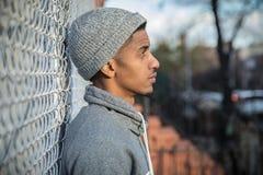 Un giovane, uomo dell'anca posa per un ritratto pensieroso lungo un recintare N fotografia stock
