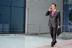 Un giovane uomo di affari sta comunicando sul telefono Immagine Stock