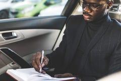 Un giovane uomo di affari in un vestito sta sedendosi nel sedile posteriore di un'automobile costosa con un taccuino Trattative d fotografie stock