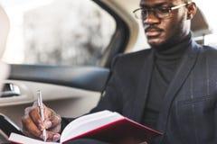 Un giovane uomo di affari in un vestito sta sedendosi nel sedile posteriore di un'automobile costosa con un taccuino Trattative d immagini stock libere da diritti