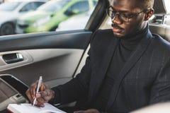 Un giovane uomo di affari in un vestito sta sedendosi nel sedile posteriore di un'automobile costosa con un taccuino Trattative d fotografia stock libera da diritti