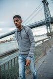 Un giovane, uomo di colore cammina lungo il ` la s East River - l'autunno 2016 di NYC Fotografia Stock