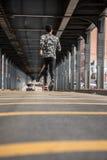 Un giovane, uomo di colore va per un trotto nelle vie di Brooklyn, NY fotografia stock