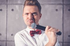 Un giovane uomo emozionale allegro divertente attraente sbatte le palpebre in una s bianca immagine stock