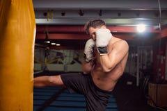 Un giovane uomo senza camicia, gamba del pugile che colpisce punching ball, practic Immagini Stock Libere da Diritti
